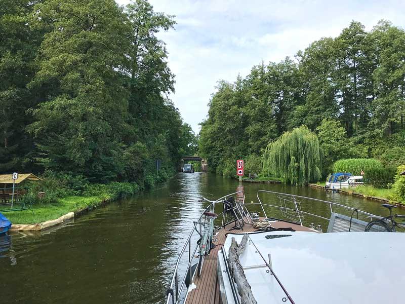 Blick über den Bug des Sportboots auf den Köriser Graben, der den Schulzensee und den Zemminsee in der Teupitzer Gewässern, Brandenburg, Dahme-Wassertraße, südlich von Berlin verbindet. Wir fahren auf eine Brücke zu, rechts davor am Ufer ein Schild, das auf eine Begegnungsverbot hinweist und zum Hupen auffordert. An beiden Ufern dichter Bewuchs mit Bäumen.