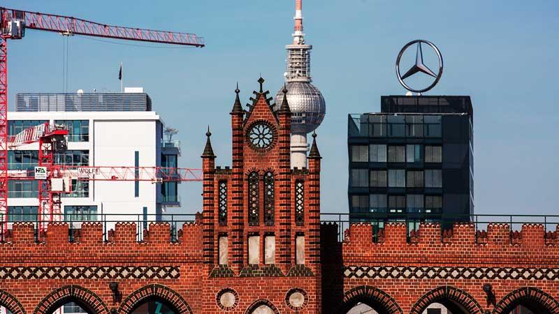 Die Oberbaumbrücke über die Spree aus rotem Backstein, dahinter die silberne Kugel des Berliner Fernsehturm Alex und ein Glasgebäude mit einem großen Mercedesstern auf dem Dach in Berlin