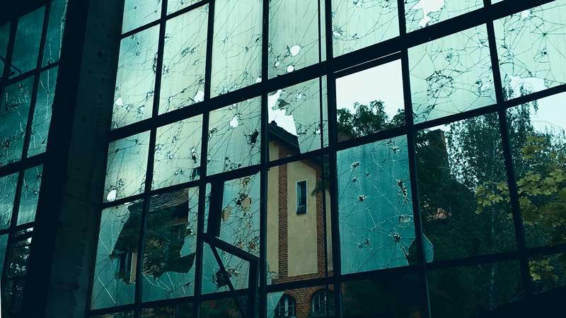 Blick durch zerlöcherte Scheiben auf zerfallene Gebäude
