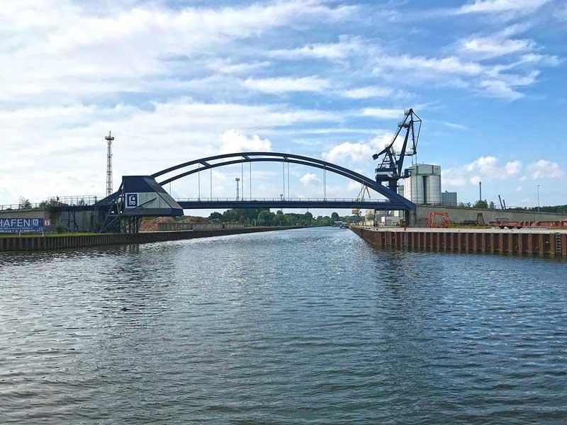 Rechterhand zweigt der Nootekanal von der Dahme-Wasserstraße ab. die Einfahrt wird von einer großen, geschwungenen Metallbrücke überspannt, dahinter Hafenanlagen. Königs Wusterhausen, Brandenburg, südlich von Berlin