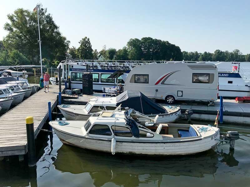 Blick vom Liegeplatz am Anleger der Dahme-Schiffahrtsgesellschaft in Teupitz am Teupitzer See, Brandenburg, auf den benachbarten Steg. Dort steht der Wohnwagen, in dem das Büro des Hafenmeisters untergebracht ist, sowie mehrere kleine Motorboote, die man mieten kann.
