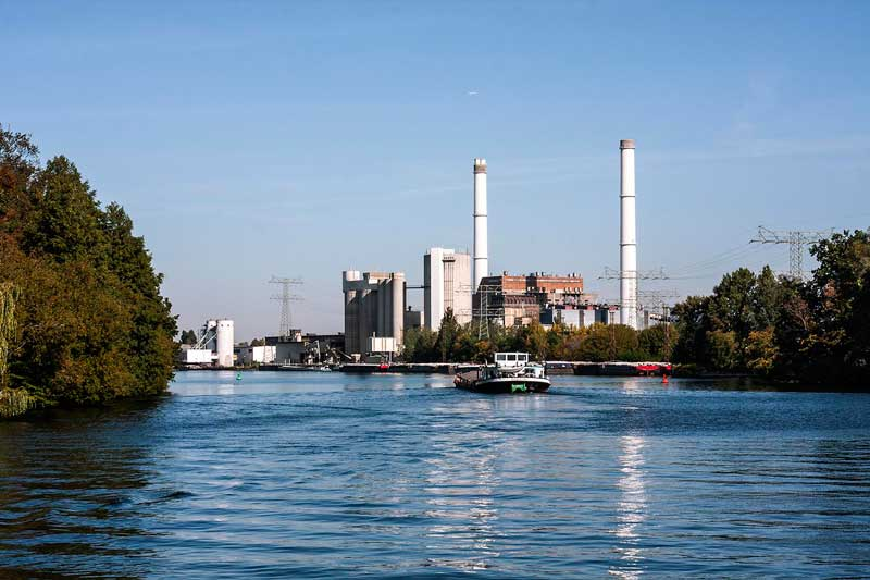 Am Ufer der Spree bei Berlin Rummelsburg ragen große Schornsteine und Indsutriebauten in die Luft, die zu einem Heizkraftwerk sowie einem Zementwerk gehören