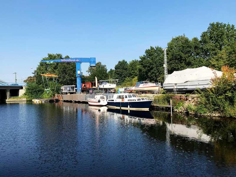 Kleine Werft mit Bootskran und Booten am Teltowkanal in Berlin