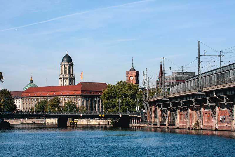 Am Ufer der Spree in Berlin verläuft rechterhand das alte, aus Ziegeln gemauerte Hochgleis der U-Bahn. Vor uns die Jannowitzbrücke über die Spree