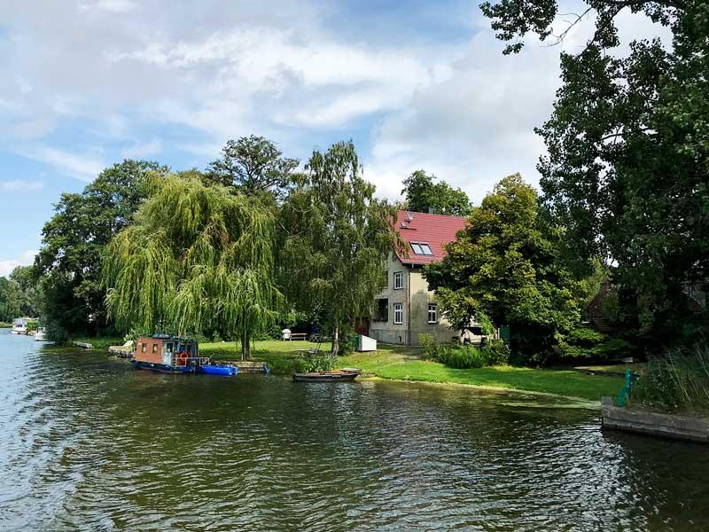 Entlang der Dahme bei Königs Wusterhausen, Brandenburg, südlich von Berlin, reichen schön gelegene Privatgrundstücke mit Trauerweiden und kleinen Bootsanlegern direkt bis ans Ufer