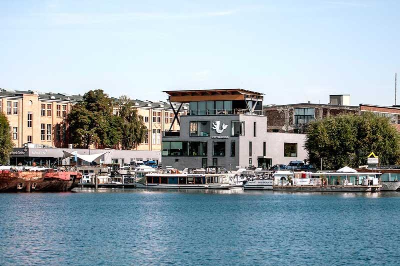 Rechterhand liegt am Ufer der Spree die City Marina Berlin Rummelsburg mit ihrem modernen Hafengebäude und dem hübschen Logo, einem Bären mit Fischschwanz