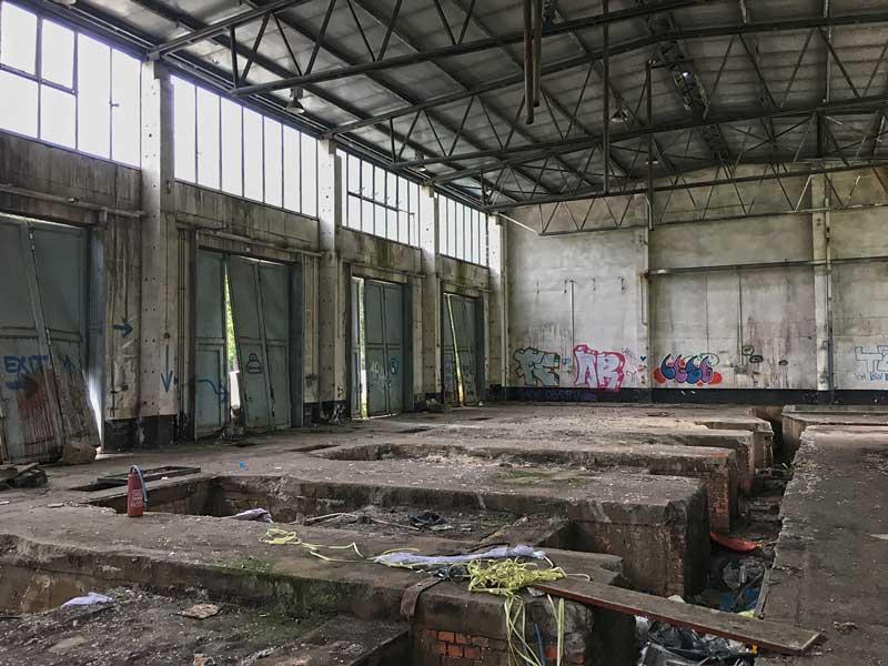 In dieser ehemaligen Maschinenhalle der Landesirrenanstalt Teupitz, Brandenburg, südlich von Berlin, hängen die Einfahrtstore schief und verbeult in ihren Aufhängungen. Die Gräben sind mit Müll übersät, die Wände mit Grafitti besprüht - Lost Places
