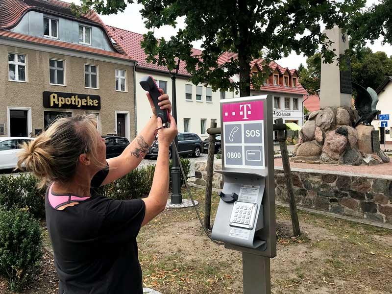 Frau hält den Hörer eines öffentlichen Münzfernsprechers, als wollte sie ein Selfie machen - Teupitz, Brandenburg