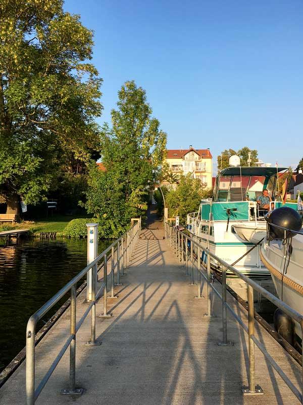 Der Anleger der Dahme-Schiffahrt in Teupitz am Teupitzer See, Brandenburg, menschenleer und im Abendlicht. Rechterhand liegen mehrere Motoryachten im Teupitzer Hafen.