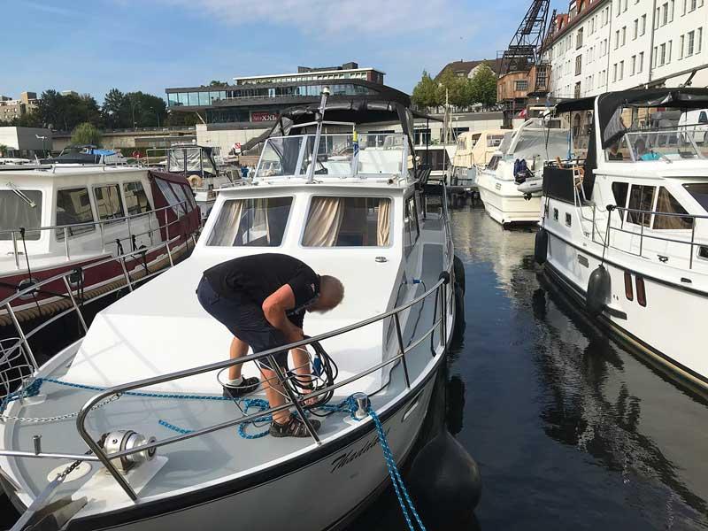 Mann auf einem Charterboot verzieht ein Stromkabel über Deck im Tempelhofer Hafen in Berlin