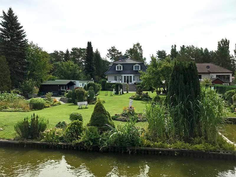 Blick auf ein Haus mit Garten bei Schwerin, Brandenburg, Teupitzer Gewässer, südlich von Berlin. Der gepflegte Garten mit Statuen reicht bis zum Ufer der Dahme-Wasserstraße