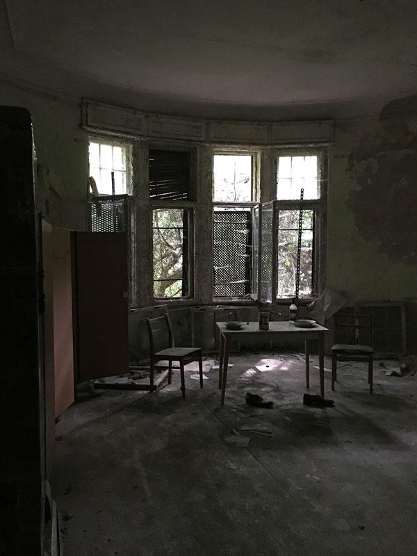 Ehemaliges Verwaltungsgebäude der Landesirrenanstalt Teupitz, Brandenburg, südlich von Berlin. Auf einem Tisch stehen zwei Teller und eine Flasche, davor auf dem Boden Schuhe. Lost Places