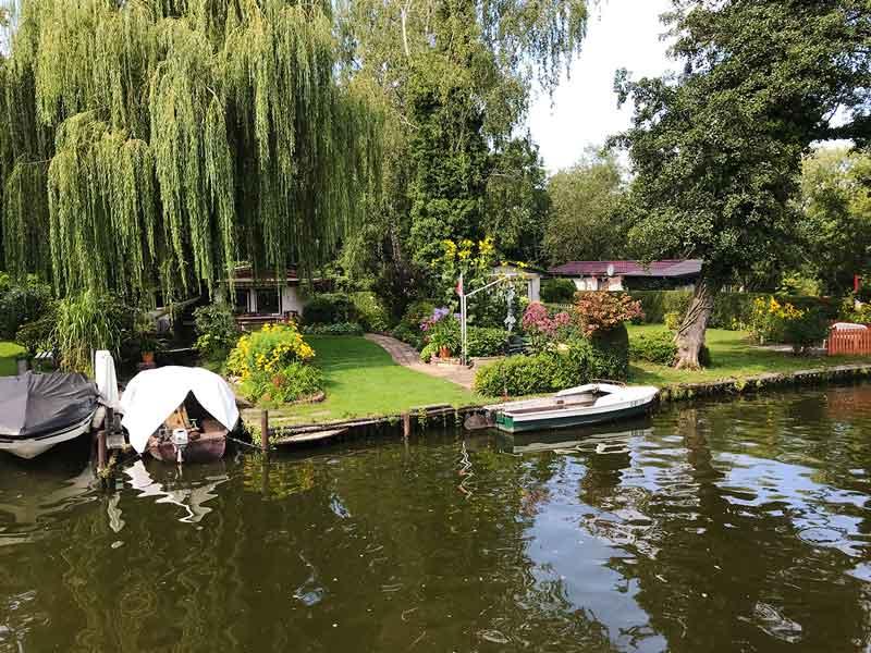 Ufergrundstücke an der Dahme-Wasserstraße in Königs Wusterhausen, Brandenburg, südlich von Berlin. Kleine Häuser, sehr gepflegte Gärten, Trauerweiden, Bootsanleger.
