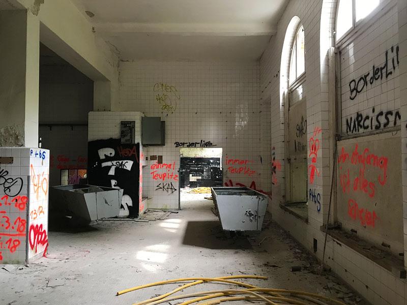 Im ehemaligen Wäschereigebäude der Landesirrenanstalt Teupitz, Brandenburg, südlich von Berlin, sind nur noch ein paar Tröge übrig. Die weißen Fliesen der Halle sind mit Grafitti besprüht - Lost Places