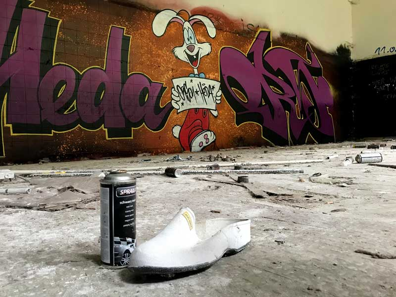 Leere Spraydose und weißer Plastikschuh vor großem Grafitto mit Cartoon Hasen in der ehemaligen Wäscherei der Landesirrenanstalt Teupitz, Brandenburg, südlich von Berlin - Lost Places