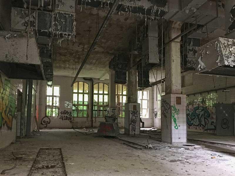 In dem sehr hohen und großen Raum der ehemaligen Wäscherei der Landesirrenanstalt Teupitz, Brandenburg, südlich von Berlin, blättert die Farbe von den Entlüstungsanlagen - Lost Places