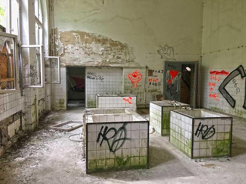 Nur noch weiß gekachelte Tröge sind übrig in diesem Raum der ehemaligen Wäscherei der landesirrenanstalt Teupitz, Brandenburg, südlich von Berlin. Alles setzt schon Moos an und ist mit Grafitte besprüht. Lost Places