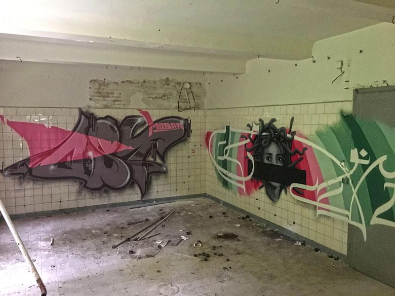 Großflächige Grafitti in einem niedrigen Raum der ehemaligen Wäscherei der Landesirrenanstalt Teupitz, Brandenburg, südlich von Berlin - Lost Places