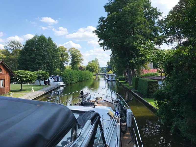 Das Boot wartet in der Kanalmitte auf die Öffnung einer sehr niedrigen Hebebrücke