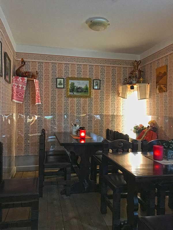 Gastraum im Restaurant, Teestube Haus 1 in der Russischen Kolonie in Potsdam, Brandenburg. Dunkle Holzmöbel, ornamentale Tapete, im unteren Bereich mit Plastik verkleidet