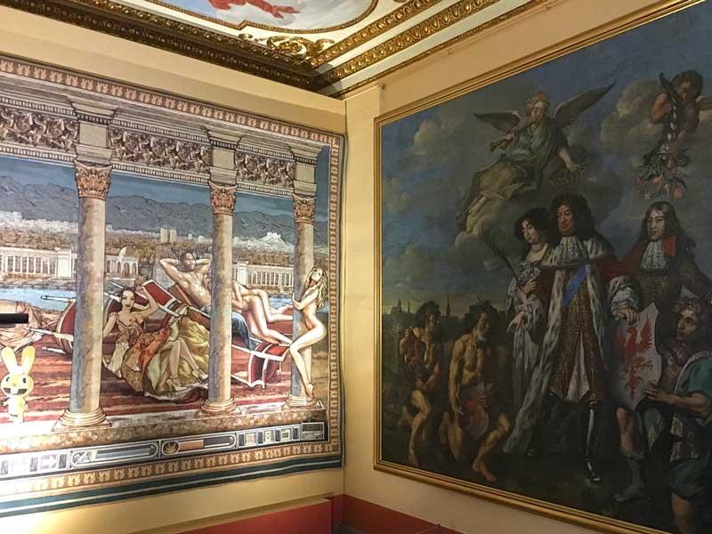 Über Eck hängen hier im Rahmen der Ausstellung B.A.R.O.C.K. im Schloss Caputh, Brandenburg, ein schwülstiges altes Barockgemälde und eine moderne, ironische Tapisserie nebeneinander