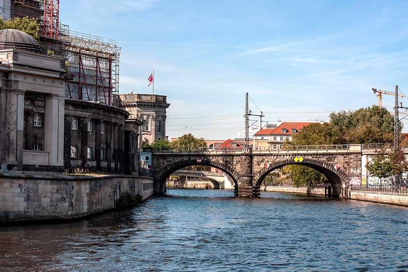 Linkerhand am Ufer der Spree in Berlin die Alte Nationalgalerie auf der Museumsinsel, dahinter zwei geschwungene alte Brücken