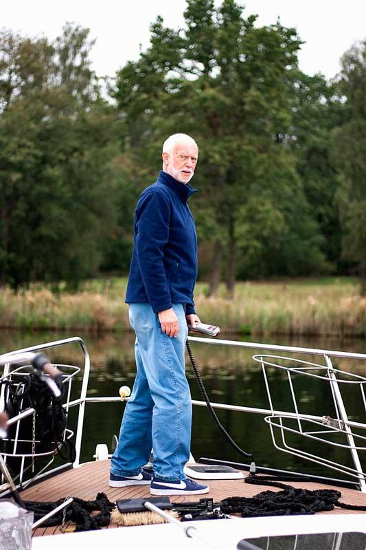 Mein Vater steht am Bug des Boots und holt mit der elektrisch bedienten Ankerwinde den Anker ein