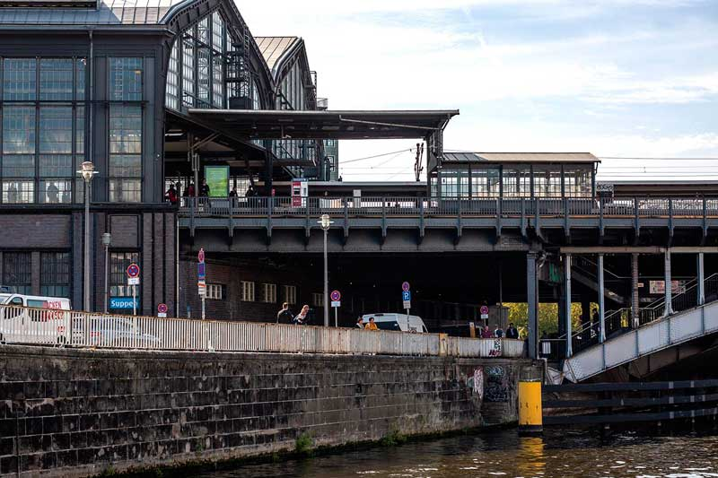 Am Ufer der Spree in Berlin erhebt sich linkerhand der Bahnhof Friedrichstraße mit seiner schönen Stahl-Glas-Konstruktion