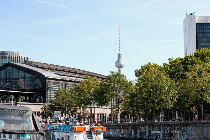Über dem Bahnhof Friedrichstraße am Ufer der Spree in Berlin erhebt sich der Fernsehturm, der Alex