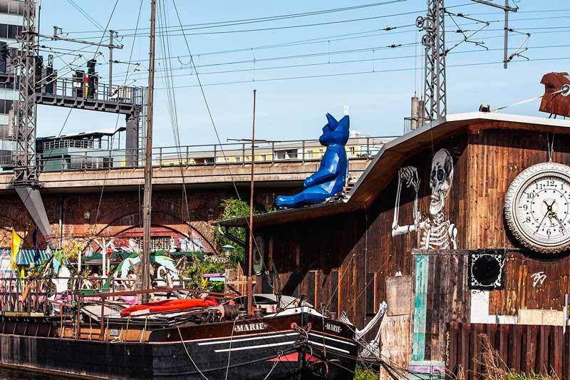 Altes Schiff mit dem Namen Marie auf der Spree vor dem Club Kater Blau. Auf einem Holzgebäude sitzen zwei Figuren auf dem Dach, eine davon anscheinend der Kater Blau