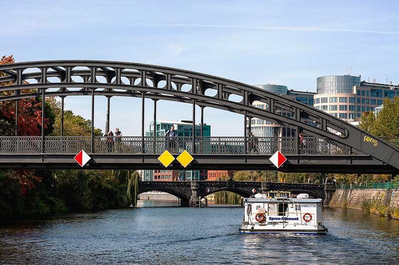 Über die Spree in Berlin erstrecken sich zwei Brücken, der Gerickesteg im Vorder- und die Moabiter Brücke in Hintergrund, vor uns ein Ausflugsschiff