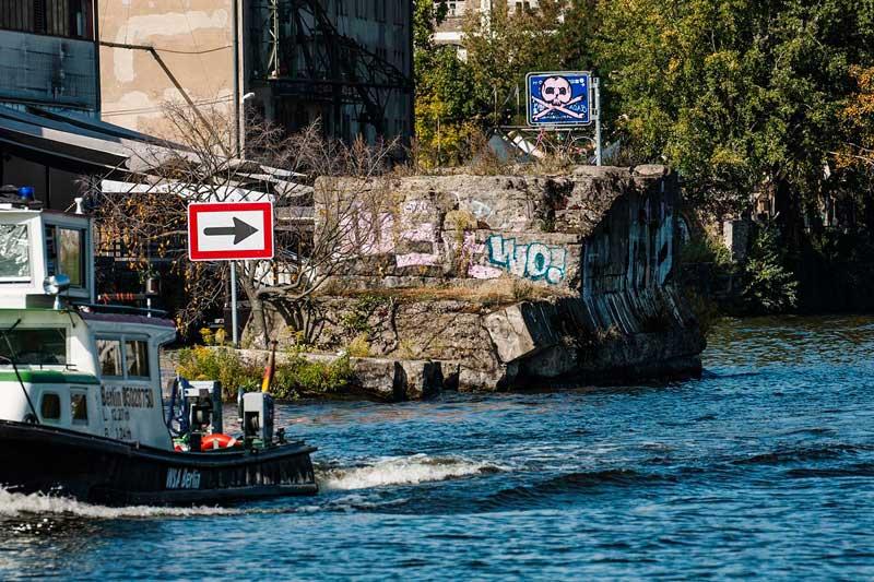 Am Ufer der Spree in Berlin Kreuzberg befindet sich eine Brückenruine, die stark mit Grafitti besprüht ist, davor ein Boot des WSA