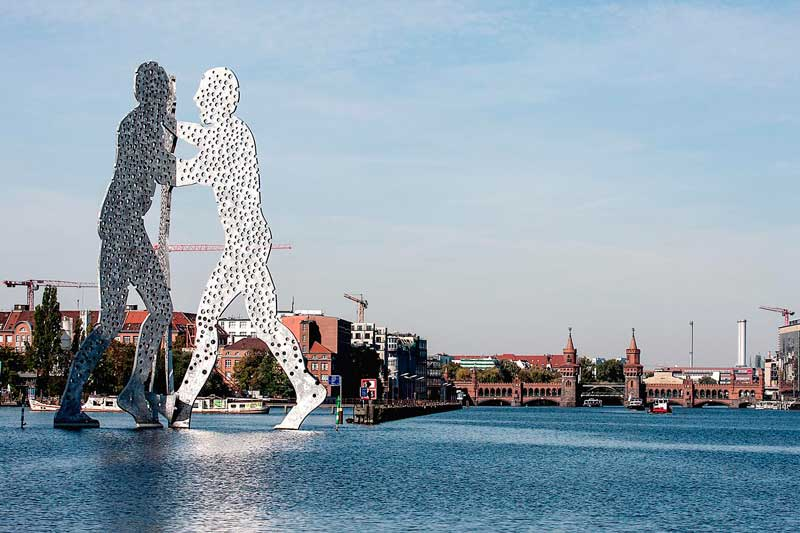 Die riesige silberne Skulptur, die am zwei Männer zeigt, steht am Osthafen Berlin in der Spree