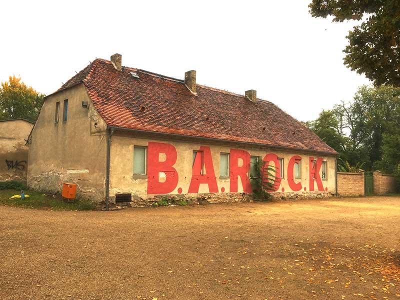 Der Titel der Ausstellung B.A.R.O.C.K. im Schloss Caputh, Brandenburg, ist mit riesigen roten Buchstaben auf eine alte Remise im Eingangsbereich gestrichen