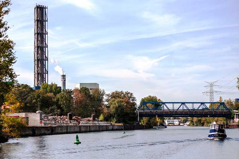 Indsutriekulisse mit rauchenden Schloten am Ufer der Spree in Berlin Ruhleben