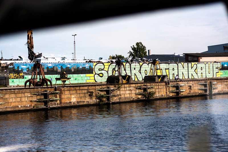 Schrottankauf steht auf einem riesigen Grafitto am Südhafen Spandau an der Spree in Berlin