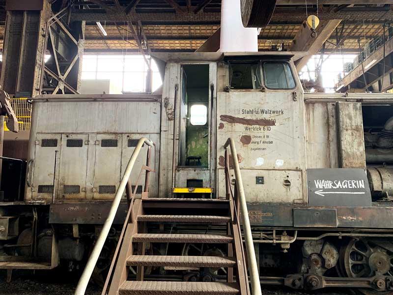 """Alte Lokomotive in der riesigen Halle des Industriemuseum Brandenburg an der Havel, an der ein Schild """"Wahrsagerin"""" hängt"""