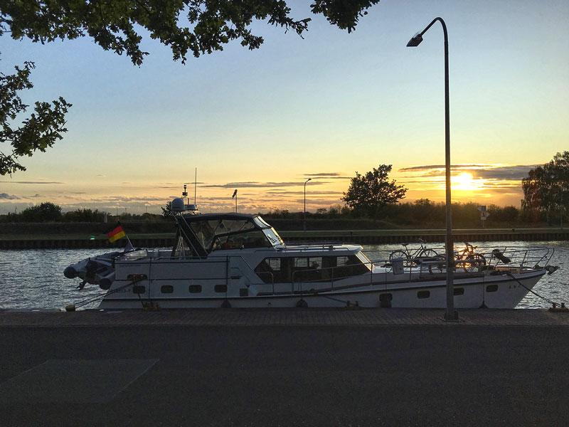 Die Motoryacht liegt an der Spundwand der Sportbootliegestelle am Wasserstraßenkreuz Magdeburg am Übergang vom Elbe-Havel-Kanal zum Mittellandkanal. Die Sonne geht gerade unter.