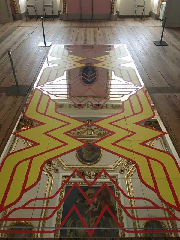 Im Rahmen der Ausstellung B.A.R.O.C.K. im Schloss Caputh, Brandenburg, liegt ein mit großen Wonderwoman-Emblemen verzierter Spiegel auf dem Boden, in dem sich das Deckengemälde und der vergoldete Stuck spiegeln