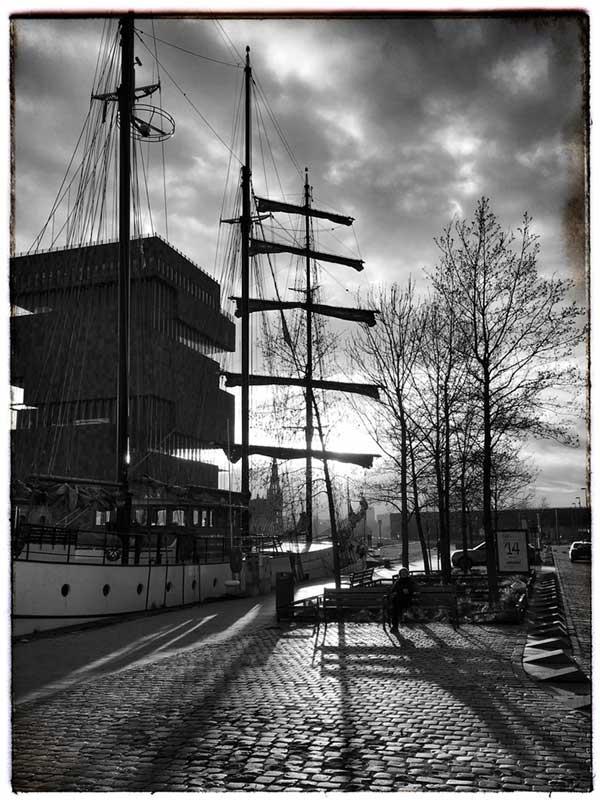 Die Sonne geht hinter dem MAS und einem historischen Dreimaster im Willemdok Antwerpen unter