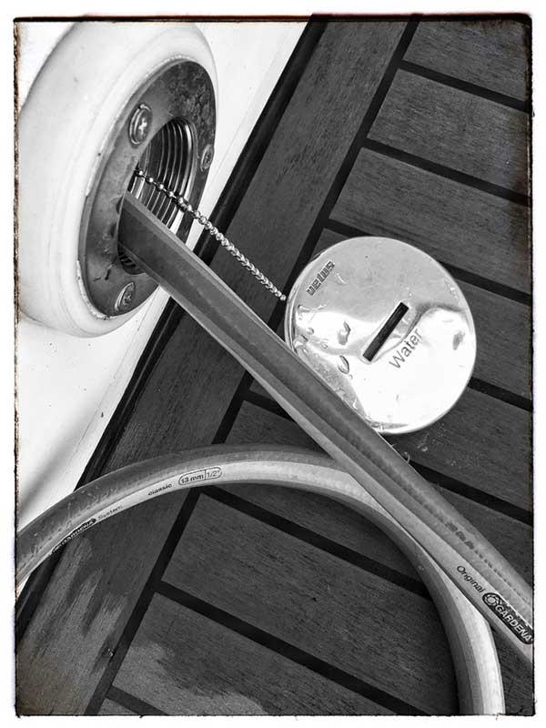 Wasserschlauch steckt in der Öffnung des Wassertanks des Boots